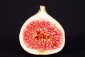 Single sectioned fresh fig on black background Royalty Free Stock Photo