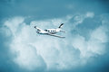 Single turboprop aircraft.. Small private plane flying in blue clouds.