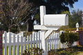 Single white mailbox sits in the front yard next to a picket fence Royalty Free Stock Photo