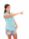 Single woman in short jeans pointing to her left Royalty Free Stock Photo
