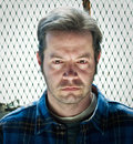 Sinister male head shot in jail or industrial setting severe lighting Stock Photography