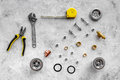Sink drain parts and plumbing tools pattern on grey stone background top view