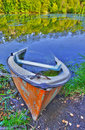 Sinking boat ashore the pond old canoe is almost sunk Royalty Free Stock Photo