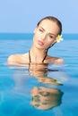 Sinnlig kvinna i blått vatten med blomman på örat Fotografering för Bildbyråer