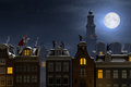 Sinterklaas and the Pieten on the rooftops at night Royalty Free Stock Photo