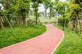 Sinuous red path in verdant spring Royalty Free Stock Photo