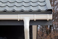 SIP panel house construction. New gray metal tile roof with white rain gutter. Royalty Free Stock Photo