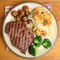 Sirloin steak dinner with dauphinois potatoes broccoli and mushrooms Royalty Free Stock Photo