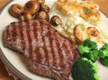 Sirloin steak dinner with dauphinois potatoes meal potates broccoli and mushrooms Royalty Free Stock Photography