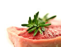 Sirloin steak macro of juicy with fresh sprigs of rosemary garnish shallow depth of field against a white background copy space Stock Images