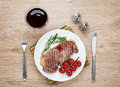 Sirloin steak with rosemary and tomatoes cherry on a plate wine view from above Stock Image