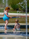 Sister and brother in a city fountain frolic under cool water on hot summer day the this landmark st joseph mi is called the Royalty Free Stock Photos