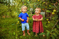 Sister and brother in the garden cute little girl with little relax near apple tree Royalty Free Stock Image