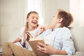 Sister and brother reading book and laughing together at home Royalty Free Stock Photo