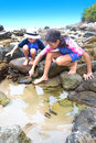 Sister and brother by a tropical rockpool Royalty Free Stock Photo