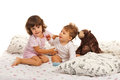 Sister embracing little brother toddler her baby in bed Stock Photos