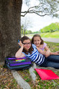 Sister firends girls relaxed under tree park after school with bag and folders Royalty Free Stock Photography