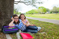 Sister firends girls relaxed under tree park after school with bag and folders Stock Images