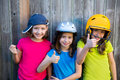 Sister and friends sport kid girls portrait smiling happy on gray fence wood backyard Royalty Free Stock Photo