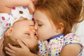 Sister kissing baby older in bed Stock Images
