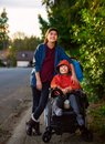 Sister standing next to disabled little brother in wheelchair outdoors Royalty Free Stock Photo