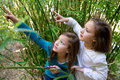 Sister twin girls playing in nature pointing finger from green canes Stock Photography