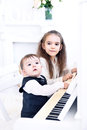 Sister and younger brother playing piano together Royalty Free Stock Images