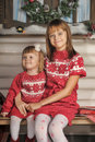Sisters on christmas time next to a tree with flowers roses and hearts Stock Photos