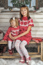 Sisters on christmas time siting under house in studio Royalty Free Stock Images