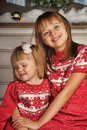 Sisters on christmas time siting under house in studio Royalty Free Stock Photos