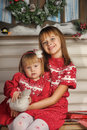 Sisters on christmas time siting under house in studio Royalty Free Stock Photo