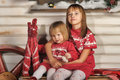 Sisters on christmas time siting under house in studio Stock Image