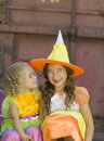 Sisters in costume halloween two happy smiling sit and laugh as they celebrate the holiday of dressed colorful costumes as a fairy Stock Photography