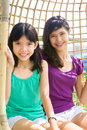 Sisters enjoying the rattan swing Royalty Free Stock Image