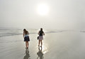 Sisters enjoying time together on beautiful foggy beach. Royalty Free Stock Photo