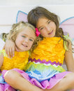 Sisters in fairy costumes halloween two happy smiling sit together on a bench dressed colorful matching preparing for Stock Photo