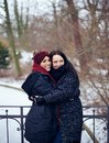 Sisters hugging in this cold winter park cheerful each other outdoors the Royalty Free Stock Photo