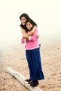 Sisters hugging on foggy beach two Royalty Free Stock Images