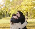 Sisters hugging girlfriends in autumn park Stock Photo