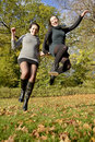 Sisters jumping laughing in autumn park Stock Photo