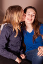 Sisters kissing young girl her smiling sister on the cheek Royalty Free Stock Photo