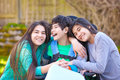 Sisters laughing and hugging disabled little brother in wheelcha Royalty Free Stock Photo