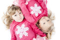 Sisters in matching winter outfits two laying next to each other happily look at the camera wearing Royalty Free Stock Photo