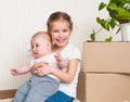 Sisters moving into new house carrying cardboard boxes and green plant Royalty Free Stock Photography