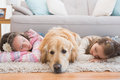 Sisters napping on rug with golden retriever Royalty Free Stock Photo