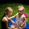 Sisters play sitting on the grass beautiful Stock Photo