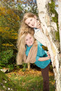 Sisters playing in the park during a nice autumn day vertical photo of young girls peeking from around tree with colors background Stock Photos