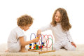 Sisters playing with wooden toy two home and sitting together on carpet Royalty Free Stock Images