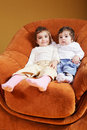 Sisters sitting in chair Royalty Free Stock Photos