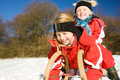 Sisters in snow on toboggan Royalty Free Stock Image